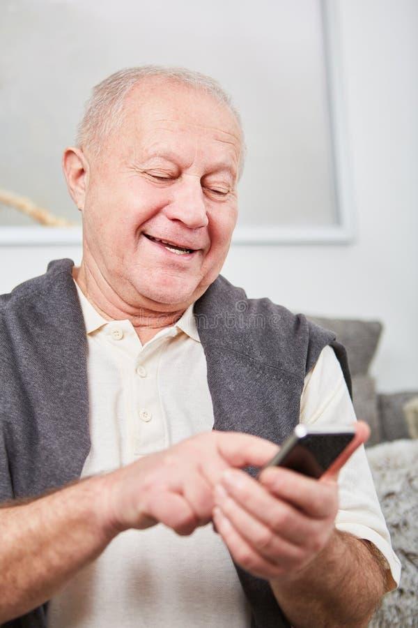 Pensionär som skriver ett meddelande eller en SMS arkivbild