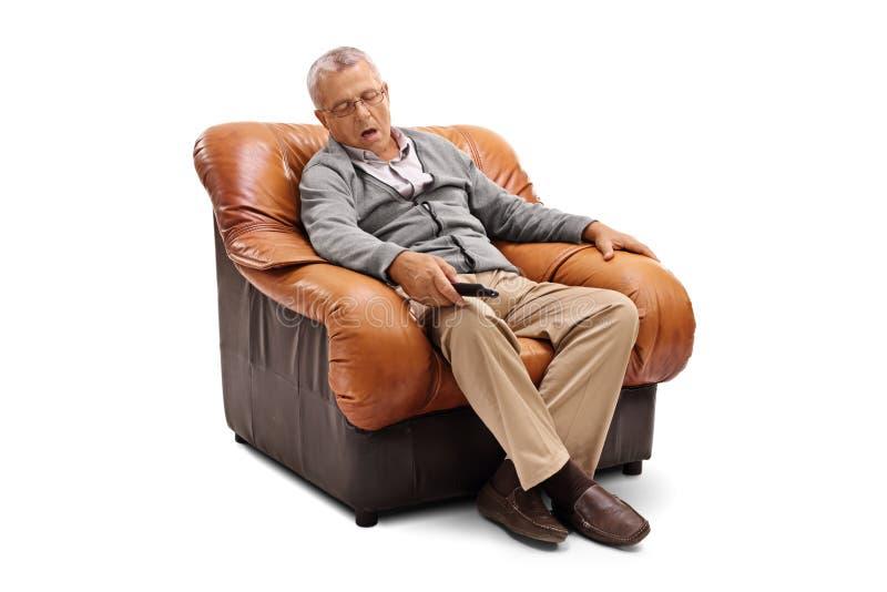 Pensionär som sover på en fåtölj royaltyfri foto