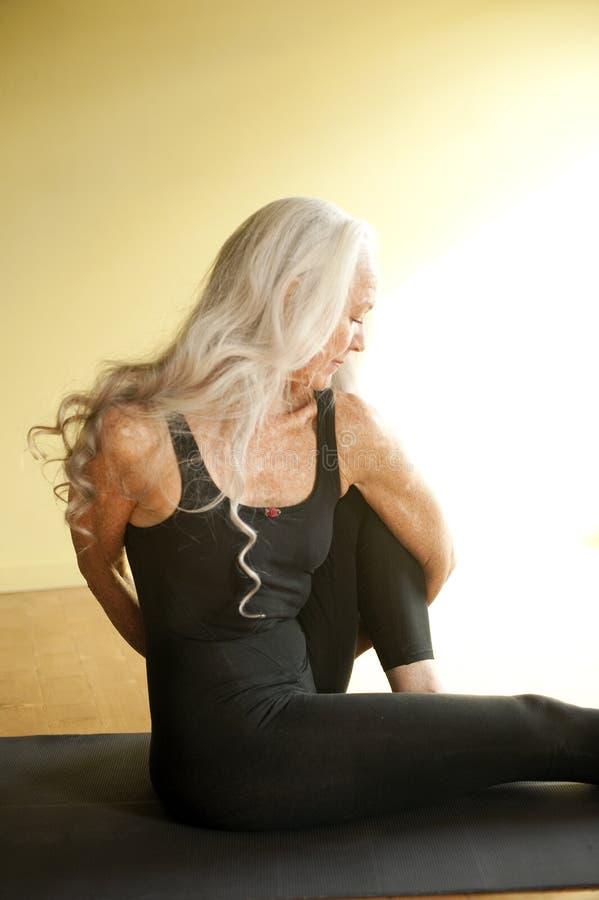 pensionär som vrider kvinnayoga royaltyfria bilder