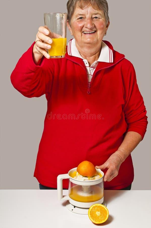Pensionär trinkt Orangensaft stockbild