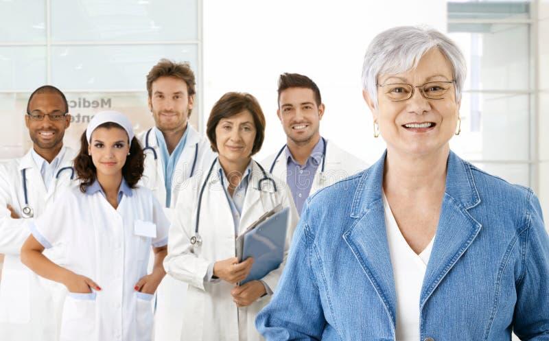 Pensionär und Ärzteteam lizenzfreie stockbilder