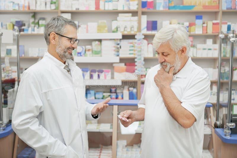 Pensionär und Apotheker, die im Drugstore sich beraten lizenzfreies stockfoto