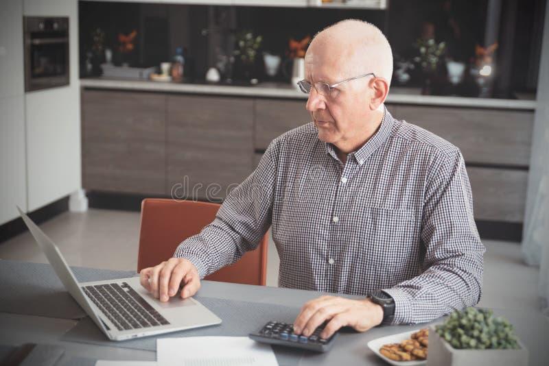 Pensionär zählt Geld, Steuerberechnungskonzept stockfotografie