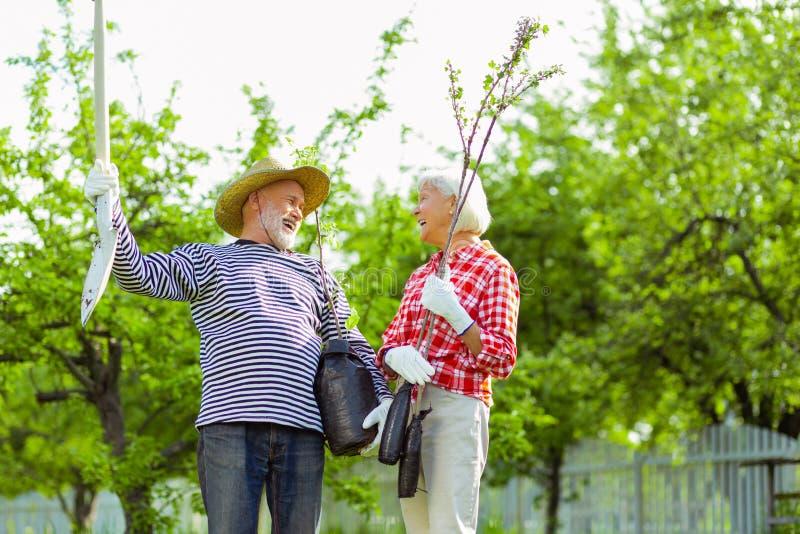Pensionäre, die bevor Bäume nahe ihrem Häuschen lachen, gepflanzt werden stockfoto