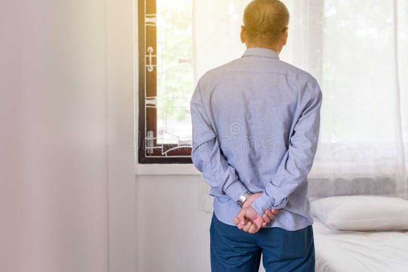 Pensionären avgår asiatiska män som har allvarligt deprimerat och ser något på fönster, mentalt hälsovårdbegrepp fotografering för bildbyråer