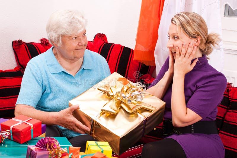 Pensionären ger gåvan till den unga nätt kvinnan arkivfoton