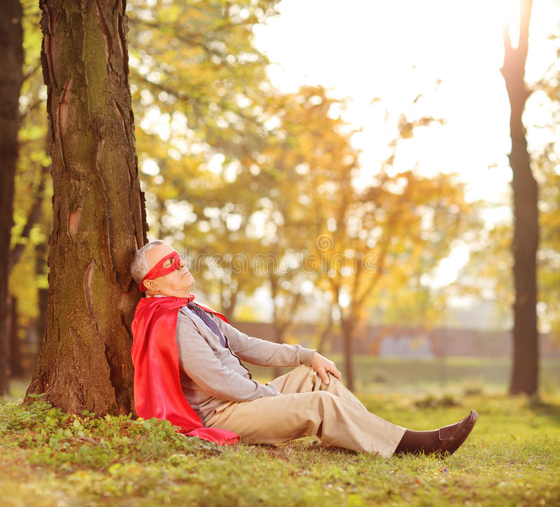 Pensionären i superherodräktbenägenhet på träd parkerar in royaltyfri bild