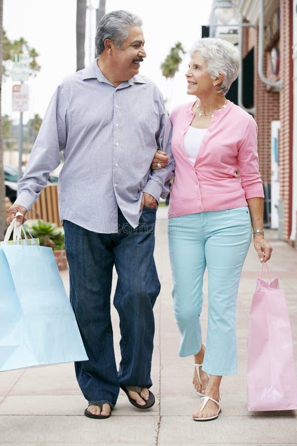 Pensionären kopplar ihop bärande shopping hänger lös arkivbild