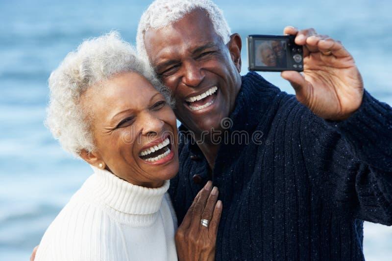 Pensionären kopplar ihop med kameran på strand royaltyfri foto