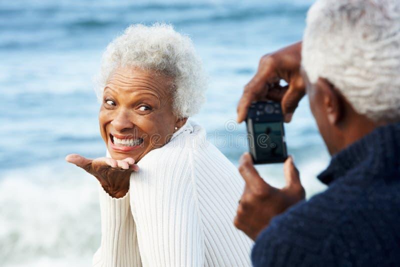 Pensionären kopplar ihop med kameran på strand royaltyfri bild