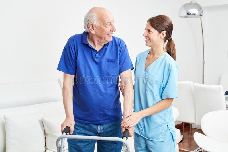 Pensionären lär att vara en patient i yrkes- terapi royaltyfria bilder