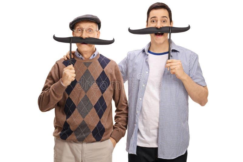 Pensionären och en ung man som poserar med stort, fejkar mustascher royaltyfria foton