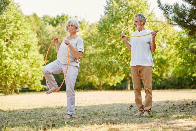 Pensionärer gör gymnastik med gummihjul royaltyfri fotografi