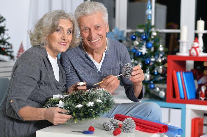 Pensionärer gör julpynt royaltyfri foto