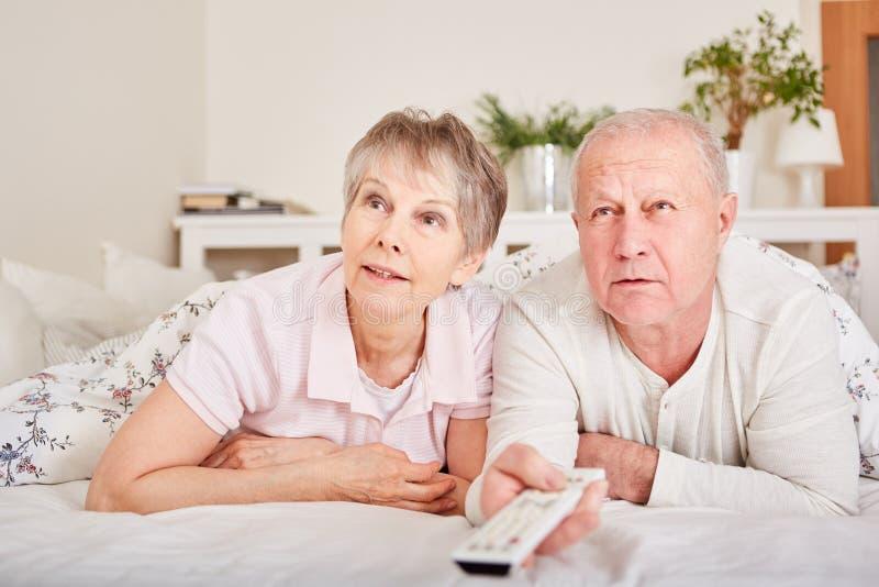 Pensionärer håller ögonen på TV i säng fotografering för bildbyråer