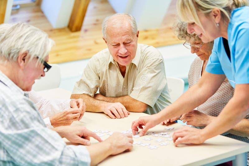 Pensionärer i avgånghemmet som spelar med pusslet royaltyfri foto