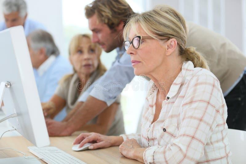 Pensionärer i beräknande grupp med instruktören arkivfoton