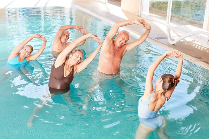 Pensionärer i pölen som gör vattenaerobics i ett seminarium royaltyfri bild