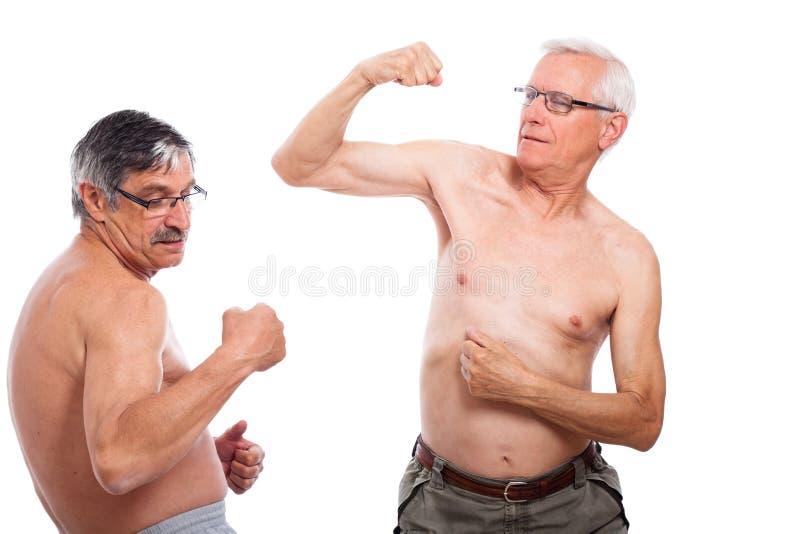 Pensionärer jämför muskler royaltyfria foton