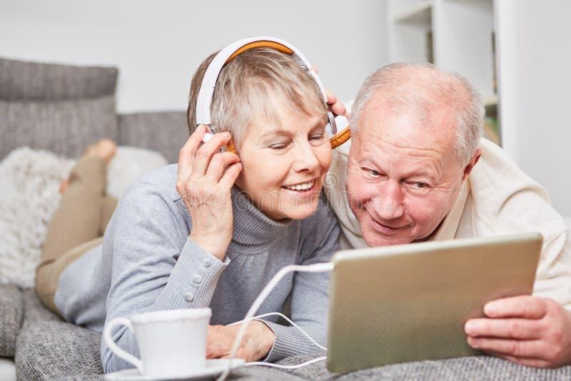 Pensionärer lyssnar till musik och kopplar av royaltyfri fotografi