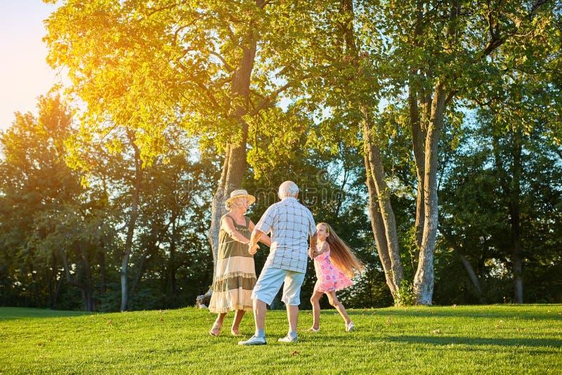 Pensionärer med barnbarnet, roundelay royaltyfria bilder