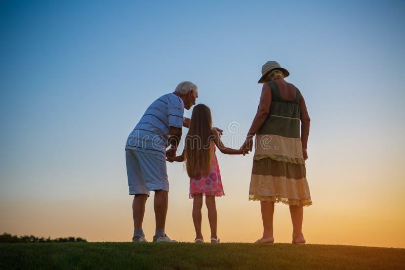 Pensionärer med barnbarnet, solnedgång royaltyfri fotografi