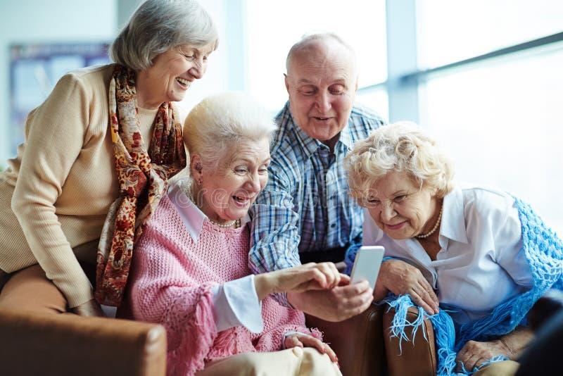 Pensionärer med smartphonen royaltyfri foto