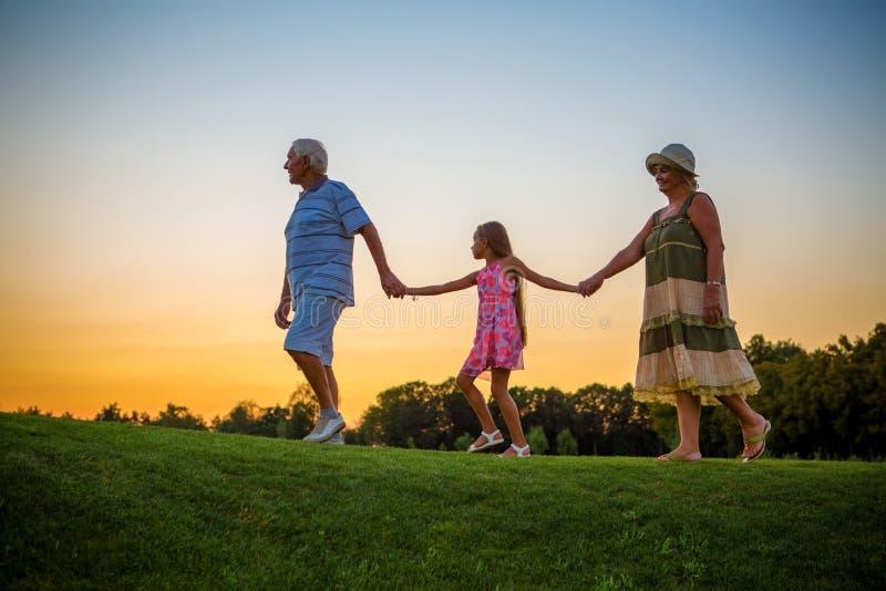 Pensionärer med sondotterinnehavhänder royaltyfria bilder