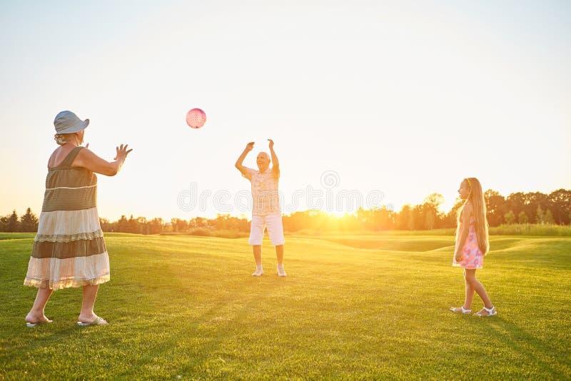 Pensionärer med sondottern som spelar bollen royaltyfri fotografi