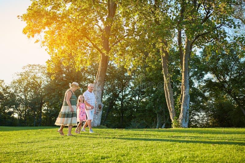 Pensionärer med sondottern som utomhus går royaltyfri bild