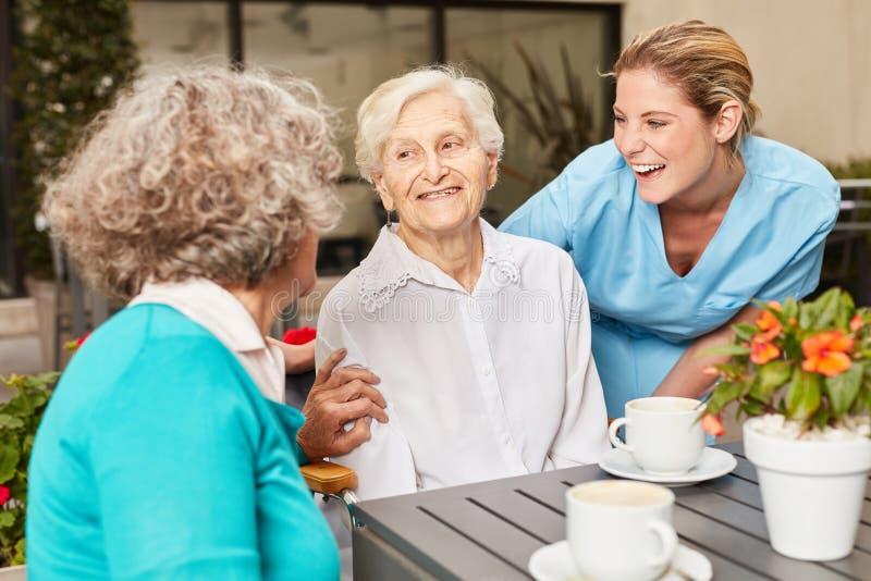Pensionärer och anhörigvårdare gör litet samtal arkivbild