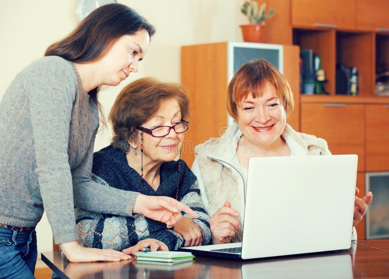 Pensionärer och relativt arbete på bärbara datorn royaltyfria bilder
