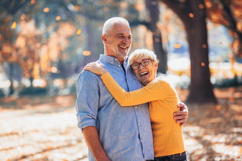 Pensionärer på en gå i höstskog arkivfoto