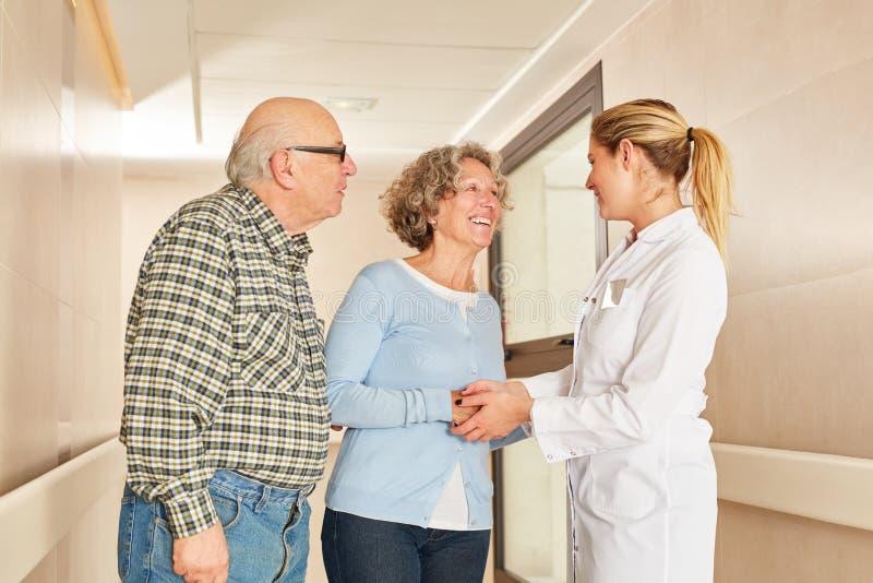 Pensionärer skakar händer med den geriatriska sjuksköterskan royaltyfri foto