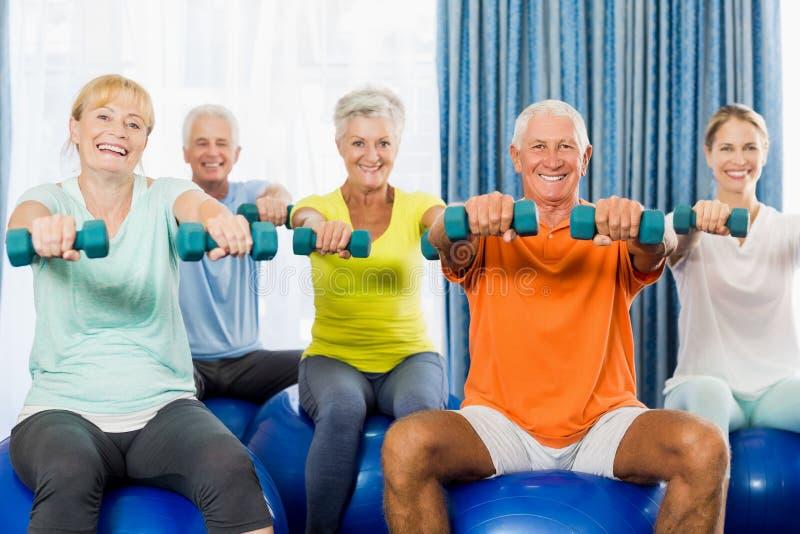 Pensionärer som använder övningsbollen och vikter royaltyfria bilder