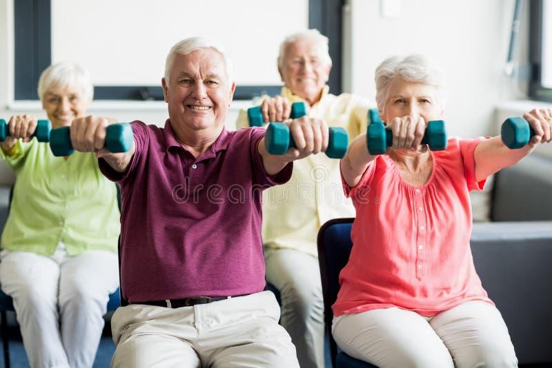 Pensionärer som använder vikter royaltyfria foton