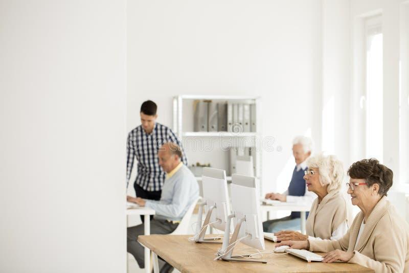 Pensionärer som arbetar på datorer royaltyfri fotografi