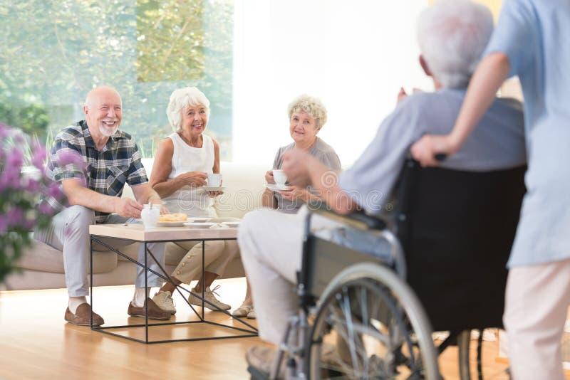 Pensionärer som besöker deras vän royaltyfri fotografi