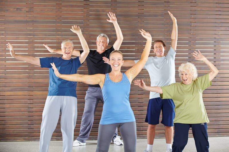 Pensionärer som dansar och övar i idrottshall royaltyfri fotografi