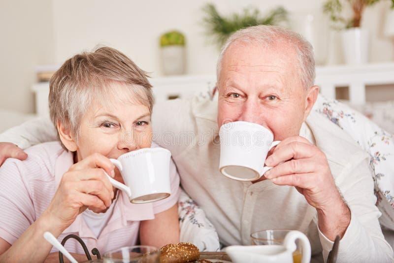 Pensionärer som dricker kaffe i säng royaltyfri fotografi