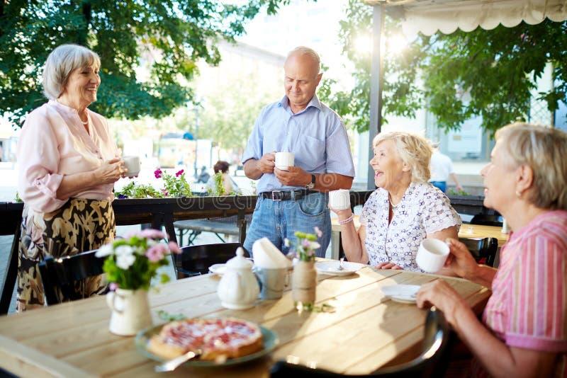 Pensionärer som firar ferie i kafé arkivbild
