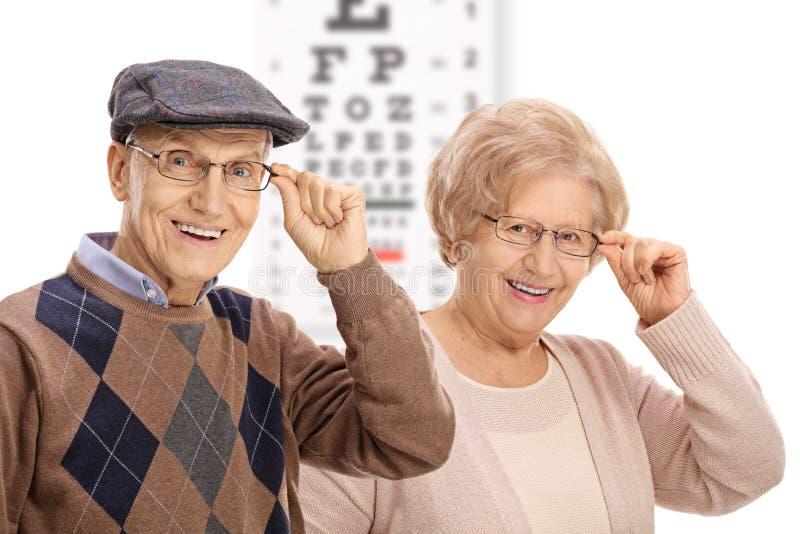 Pensionärer som framme ler av ett ögondiagram arkivbilder