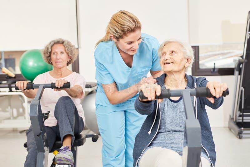 Pensionärer som gör ergometerutbildning i rehab arkivbilder