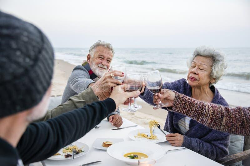 Pensionärer som har ett matställeparti på stranden arkivbild