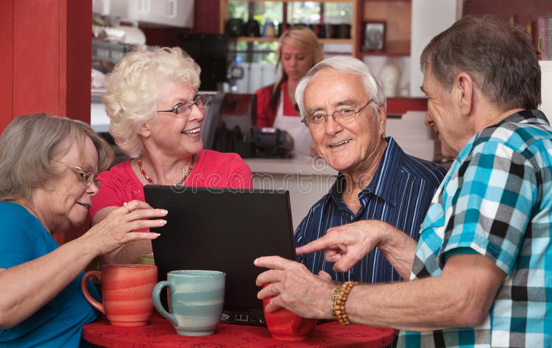 Pensionärer som har gyckel med datoren i Cafe arkivfoton