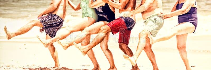 Pensionärer som i rad dansar på stranden royaltyfria bilder