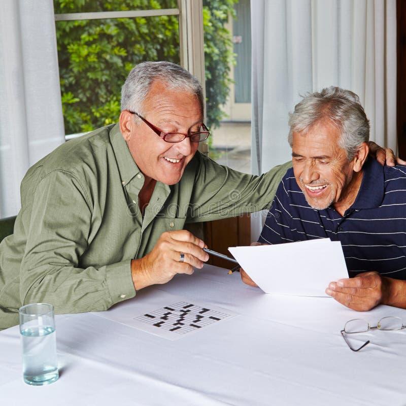 Pensionärer som löser gåtor royaltyfri fotografi