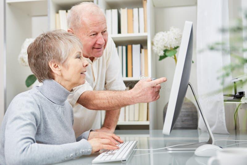 Pensionärer som par lär om datoren royaltyfri fotografi