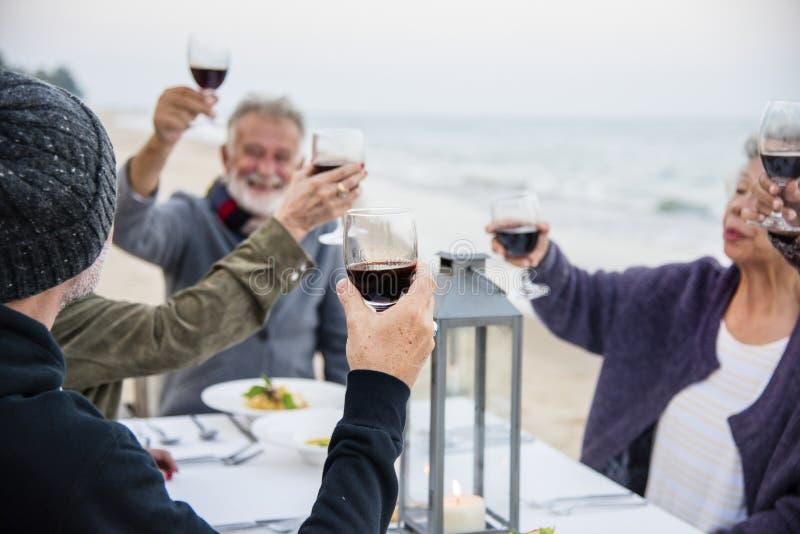 Pensionärer som rostar med rött vin på stranden arkivfoto