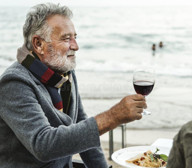 Pensionärer som rostar med rött vin på stranden arkivfoton